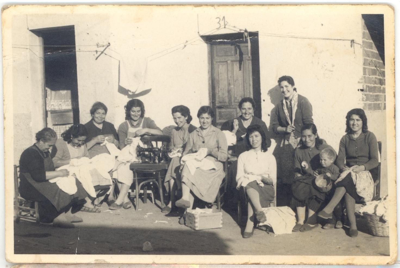 Grupo de vecinas cosiendo delante de sus casas en corrillo amable ...